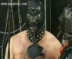 Masked mistress puts rope around cock and balls of slave and
