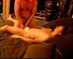 Beefy younger dude gets balls bashed in white briefs by older man.